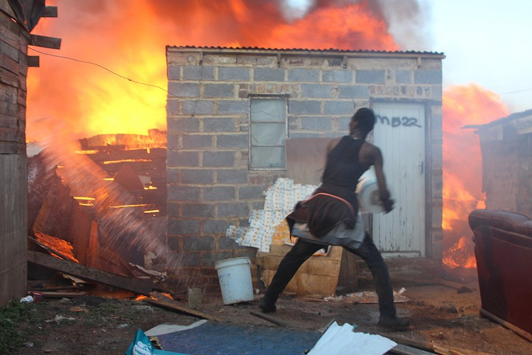 A man uses buckets of water to fight a shack fire which broke out in Mangolongolo informal settlement near Denver in eastern Johannesburg. (Photograph by: Magnificent Mndebele)