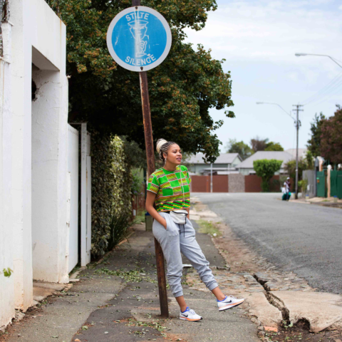 """9 January 2019. Gqom artist Sho Madjozi relaxes against a """"Silence"""" sign in Brixton Johannesburg. Far from quiet Madjozi has shifted the landscape of what language can do in popular culture."""