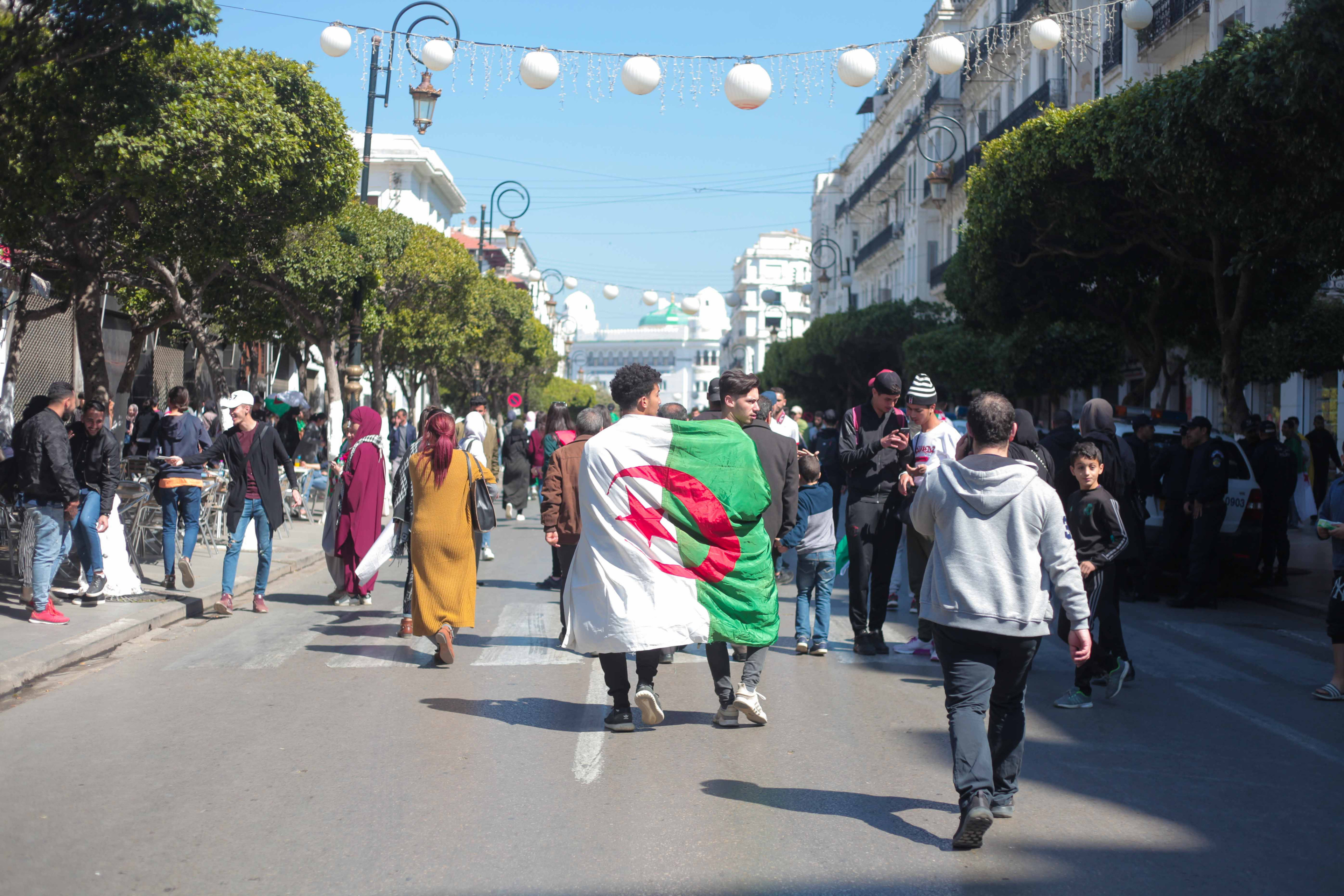 12 March 2019: Two friends wrapped in the Algerian flag march in front of the University of Algiers during student protests, which have taken place every Friday for the past month. (Photographs by Maher Mezhai)