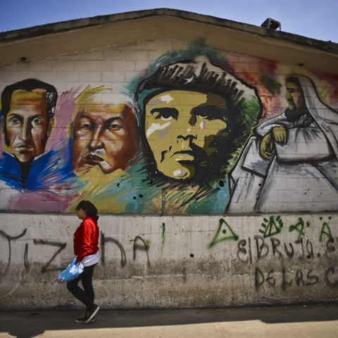 16 January 2013: A woman walks past a graffiti mural depicting (from left) Simon Bolivar, former Venezuelan President Hugo Chavez, Che Guevara and Jesus Christ in downtown Caracas, Venezuela. Photography: Meridith Kohut/Bloomberg via Getty Images