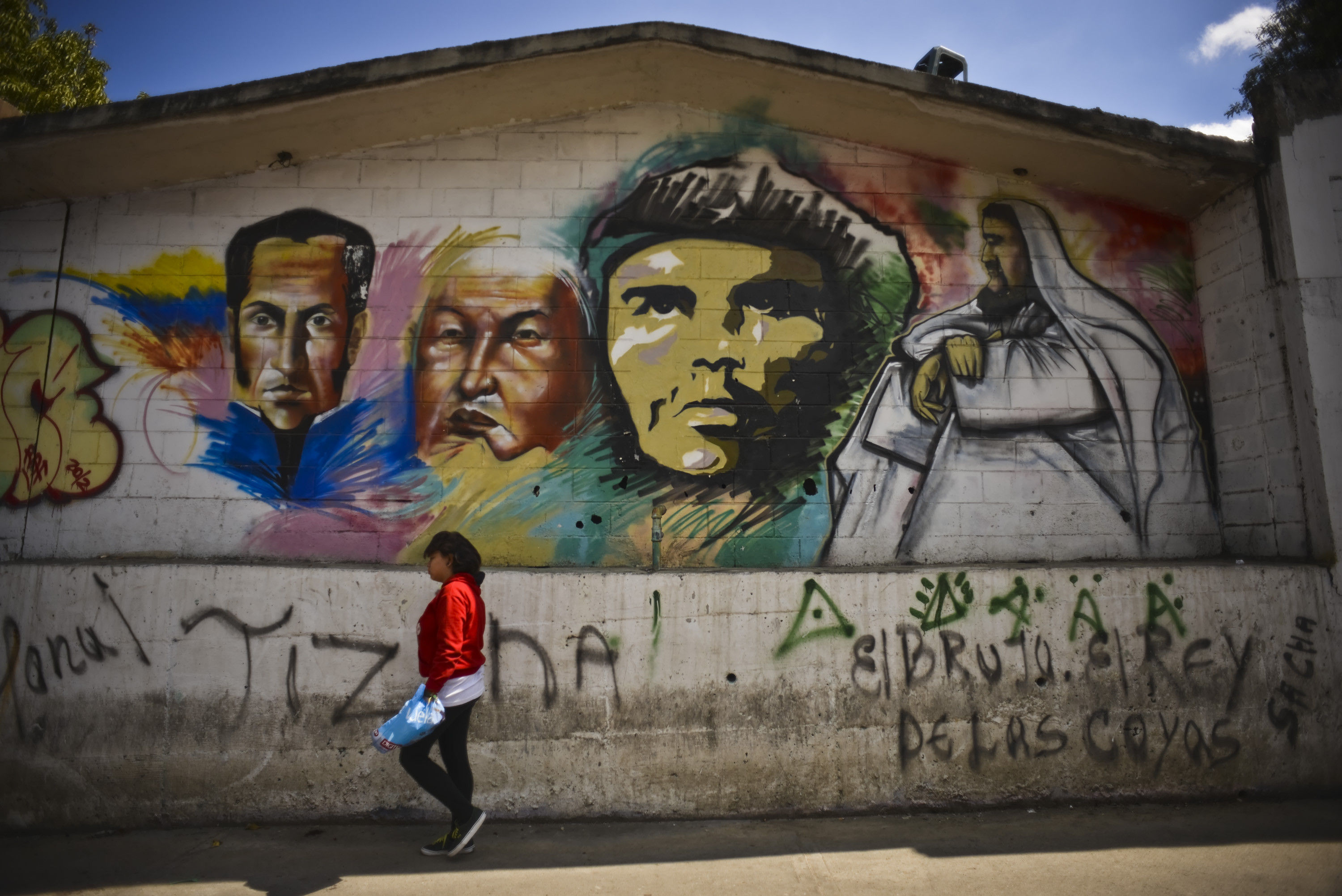16 January 2013: A woman walks past a graffiti mural depicting (from left) Simon Bolivar, former Venezuelan President Hugo Chavez, Che Guevara and Jesus Christ in downtown Caracas, Venezuela. Photography: Meridith Kohut/Bloomberg via Getty Images