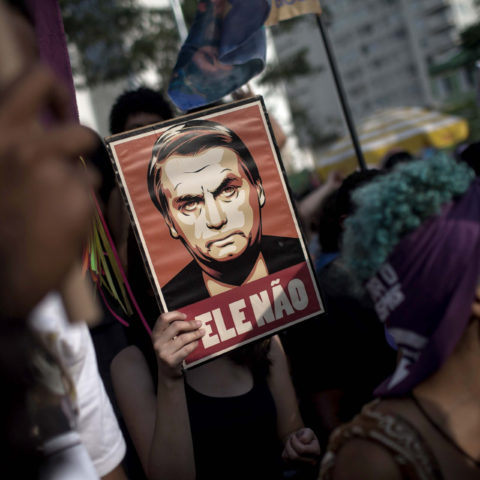 29 September 2018: Protesters in Sao Paulo, Brazil carry posters depicting the far-right candidate for president Jair Bolsonaro. (Photo by Victor Moriyama/Getty Images)
