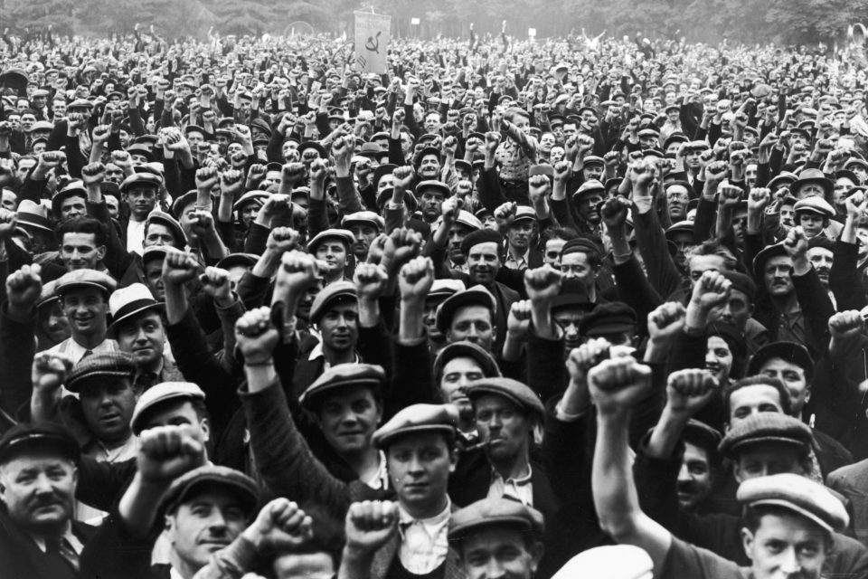 13 June 1936: Striking building workers raise their fists in salute during a rally in the Bois de Vincennes, Paris. (Photograph by Keystone/Hulton Archive/Getty Images)