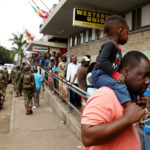 16 January 2019: Armed soldiers patrol as people queue to shop at a supermarket in Harare, Zimbabwe. (Photograph by Reuters/ Philimon Bulawayo)