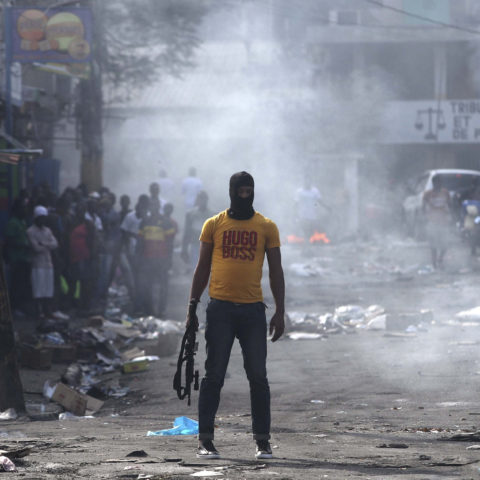17 February 2019: A man in a balaclava holds an assault rifle as he stands in a smoke-filled street during anti-government protests in Port-au-Prince, Haiti. (Photograph by Reuters/Ivan Alvarado)