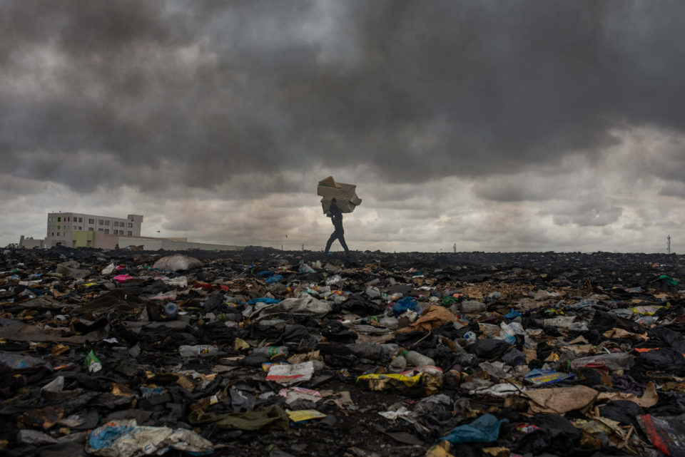 27 September 2018: A worker at Agbogbloshie carries material over an area which used to be a wetland.