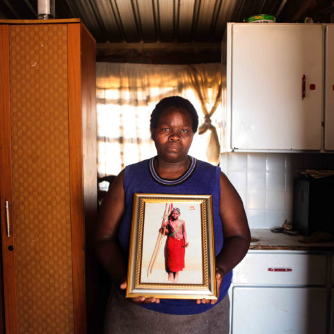 21 December 2017: Nombuyiselo Ntlane at her home in Snake Park where she holds a photograph of her son, Siphiwe. He was shot dead by a migrant spaza-shop owner when he was 14. (Photograph by Oupa Nkosi)