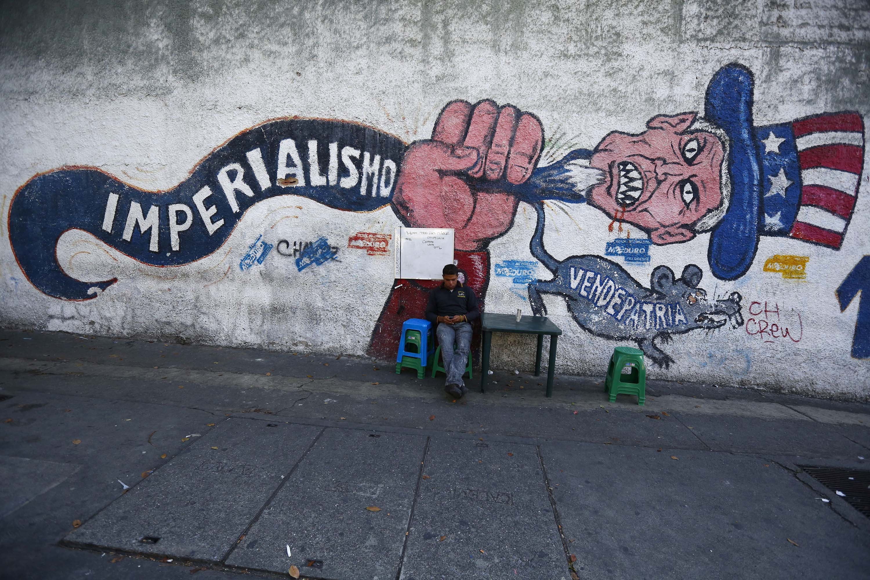 "9 March 2015: A man sits in front of graffiti, which reads ""imperialism"" in Caracas, after the United States ordered sanctions against seven officials from the oil-rich country. (Photograph by Jorge Silva/Reuters)"