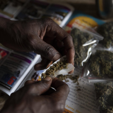 20 November 2018: Bongi rolling a joint with bags of dagga that he sells in the background. Mpondoland is famous for Mpondo Gold, the fabled endemic strain of cannabis sativa.