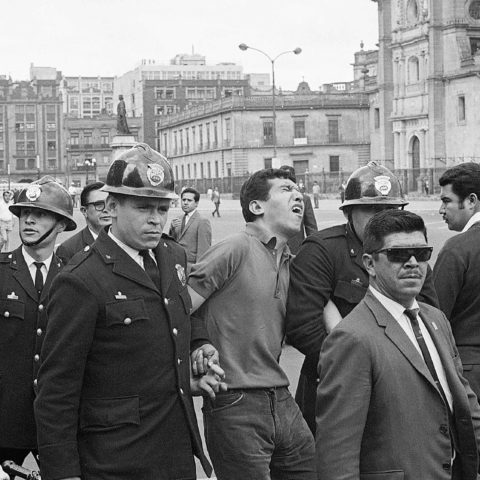 28 August 1968: A police officer escorts a demonstrator from Mexico City's Central Plaza during an anti-government rally. Riot police and soldiers opened fire to break up the protest. (Photograph by Bettmann/Contributor)