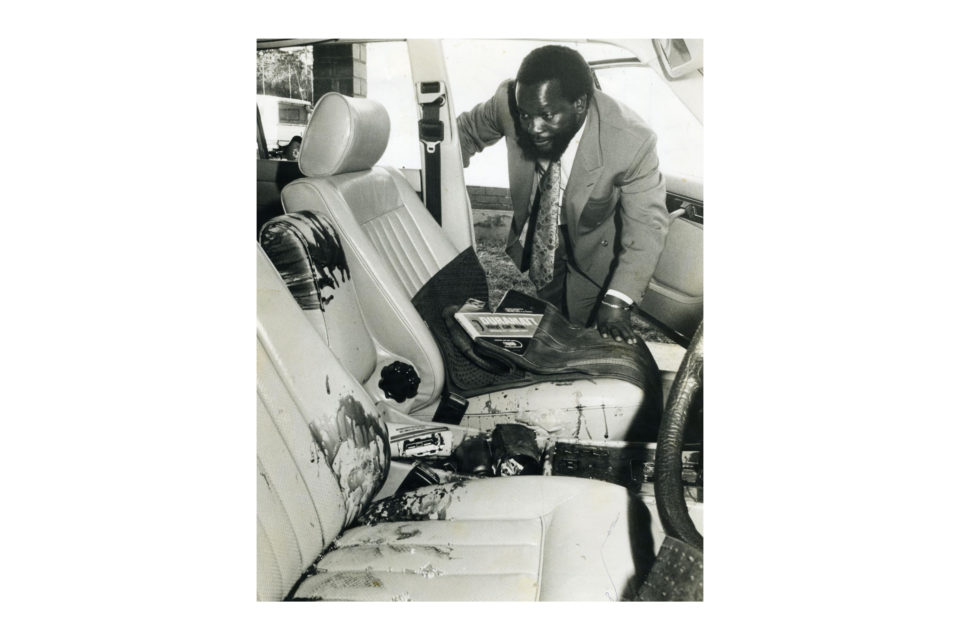 1990: Mhlabunzima Joseph Maphumulo inspects his car after an attempt on his life that resulted in the deaths of Alson and Nelson Kunene. (Photograph courtesy Jill Kelly/ The Witness)
