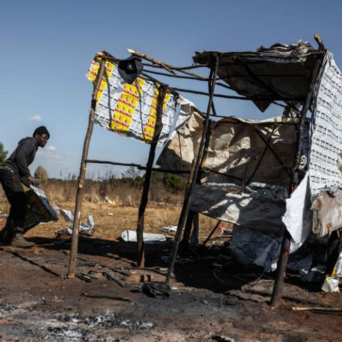 Bongani Siwela rebuilds his shack with paper after it was demolished by the Ekurhuleni Metro Police Department during an eviction.