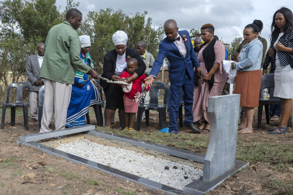 15 September 2018: Mnqobi Mjanyelwa, (centre blue suit) Mjanyelwa's first-born son pays his final respects at his fathers grave at their homestead in Dindini, near Bizana in the Eastern Cape.