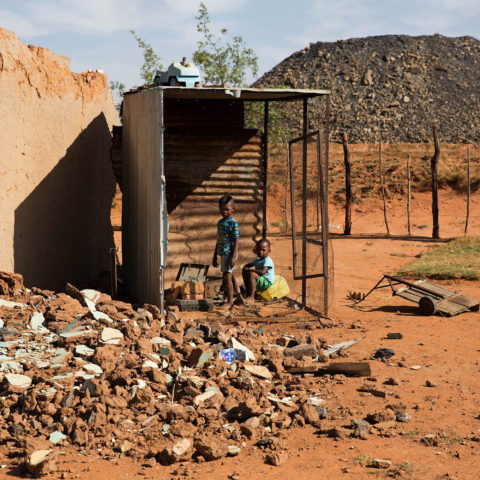 11 October 2016. Two boys play in the remains of a house in Arbor. A coal mine has sprung up and begun encroaching on the settlement.