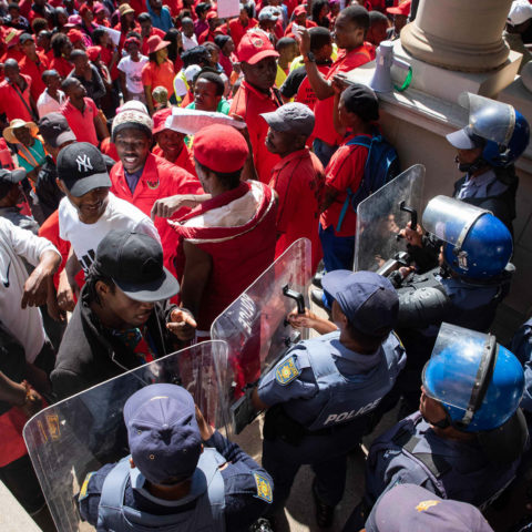 8 October 2018: Abahlali baseMjondolo members face off against the police outside the Durban City Hall. Protestors marched from Curries Fountain to the City Hall in protest against the ongoing killing of its members.