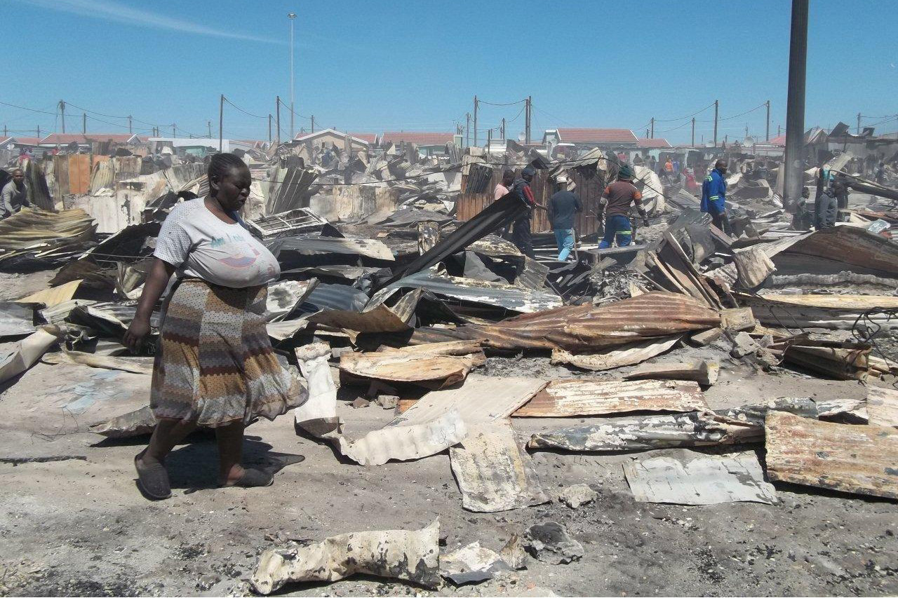 20 October 2018: Nomveliso Gxiya wanders through the rubble of what used to be her home In SST Section in Khayelitsha, Cape Town (Photograph by Vincent Lali)