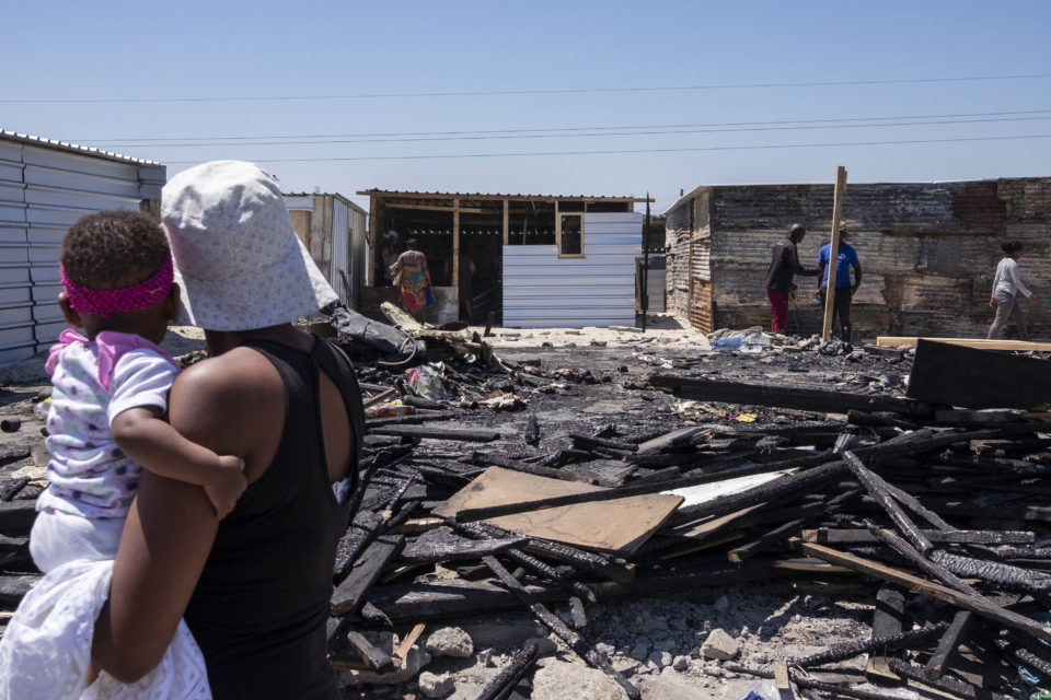 25 October 2018: A woman and child gaze at the destruction caused by the fire that destroyed hundreds of homes in Khayelitsha.