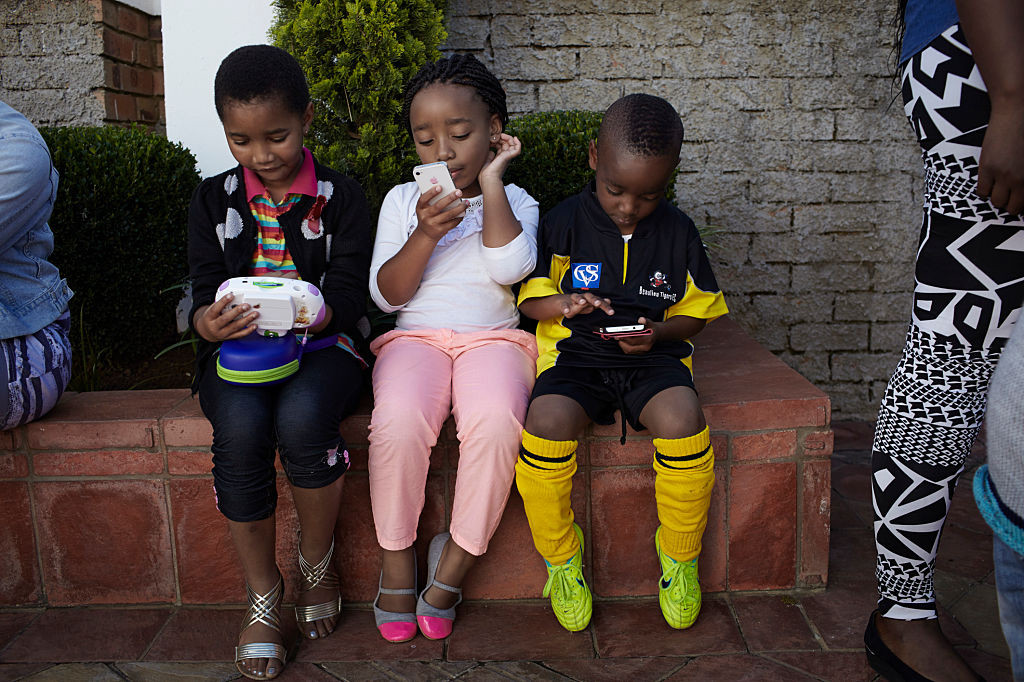 27 April 2013: Children use mobile phones while their mothers shop at a market in Soweto. (Photograph by Per-Anders Pettersson/Getty Images)