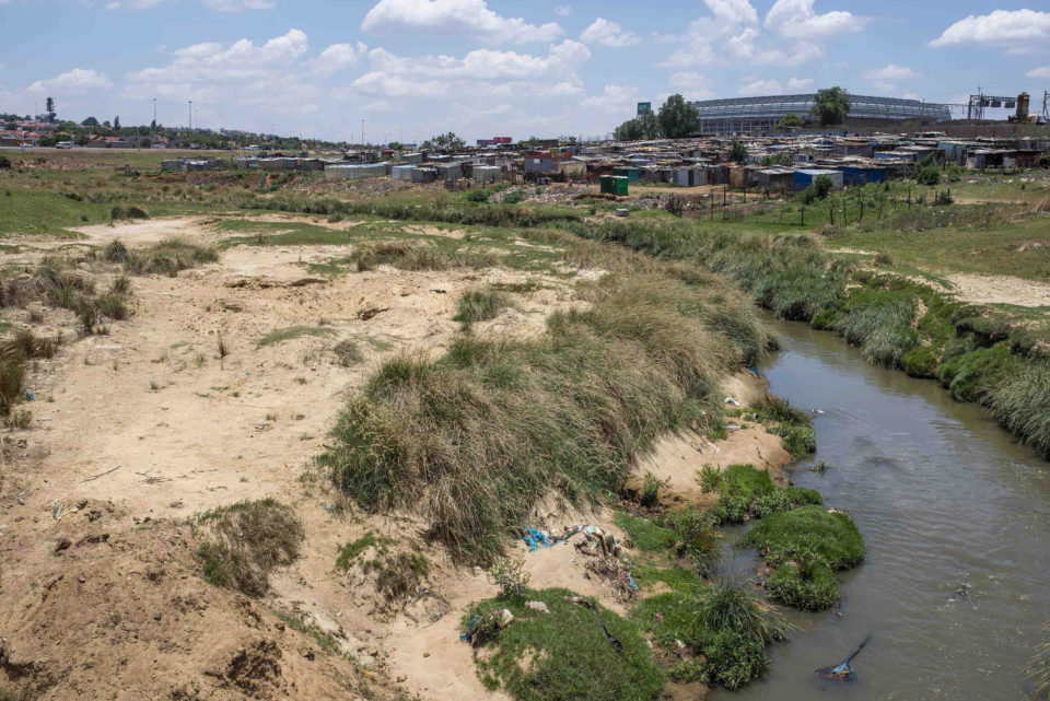 27 November 2018: A general view of the Imbuzini shack settlement and Orlando Stadium in Soweto. The settlement is home to hundreds of people living on the banks of the Klipriver.