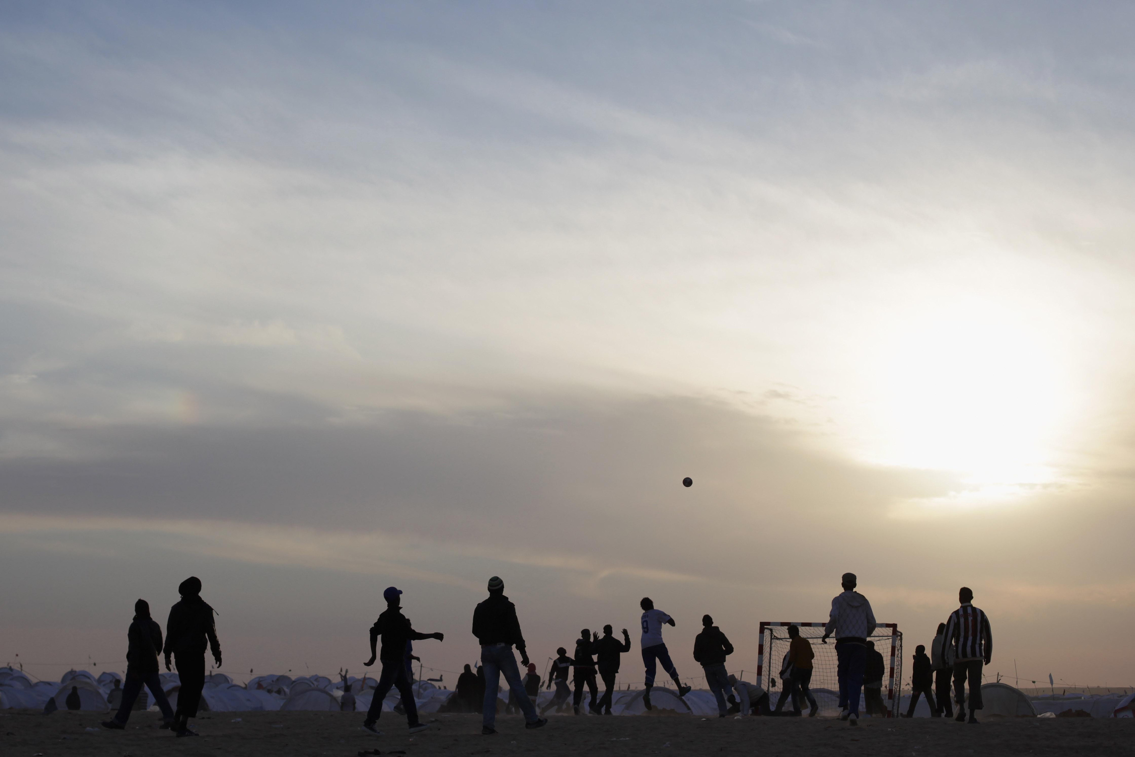 11 March 2011: Men play football at a United Nations displacement camp in Ras Jdir, Tunisia. Tens of thousands of refugees fled to the Tunisian border to escape the fighting in and around the Libyan capital of Tripoli. (Photo by Dan Kitwood/Getty Images)