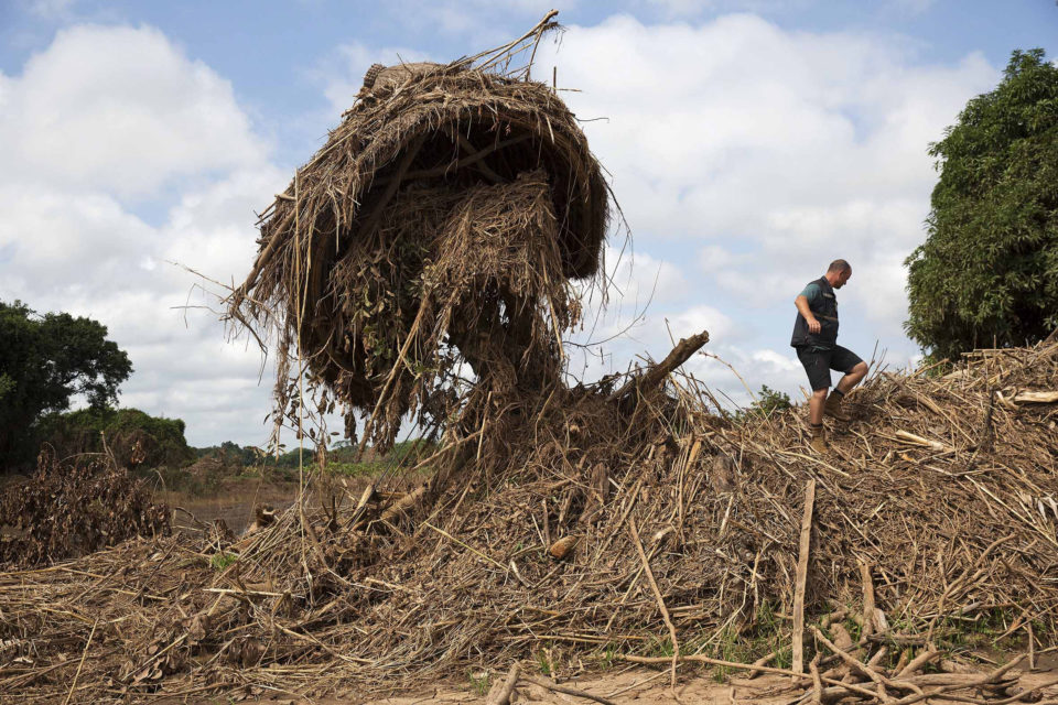 31 March 2019: Stephen Fonseca searches a pile of debris in a flooded village near Dombe.