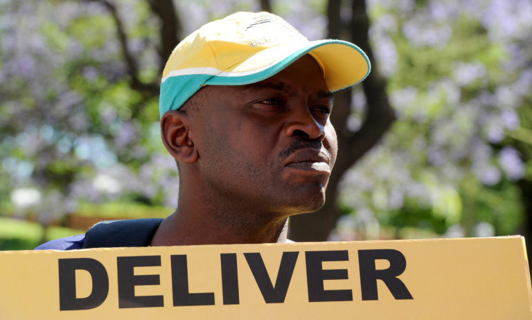 A man displays a placard while participating in a Cosatu march in Johannesburg against the implementation of e-tolls, a better public transport system as well as the banning of labour brokers and the scrapping of the youth wage subsidy, Thursday, 14 November 2013. Picture: Werner Beukes/SAPA
