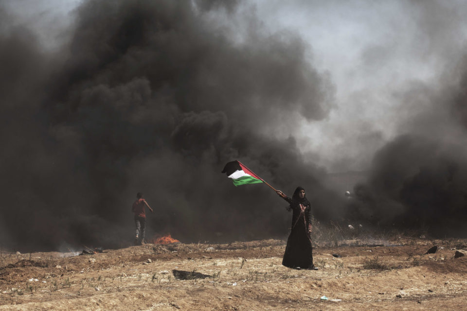 14 May 2018: A woman waves a Palestine flag in Gaza City. Israeli soldiers killed at least 41 Palestinians and wounded more than 1 000 as demonstrations coincided with the US embassy opening in Jerusalem. (Photograph by Etienne De Malglaive/Getty Images)