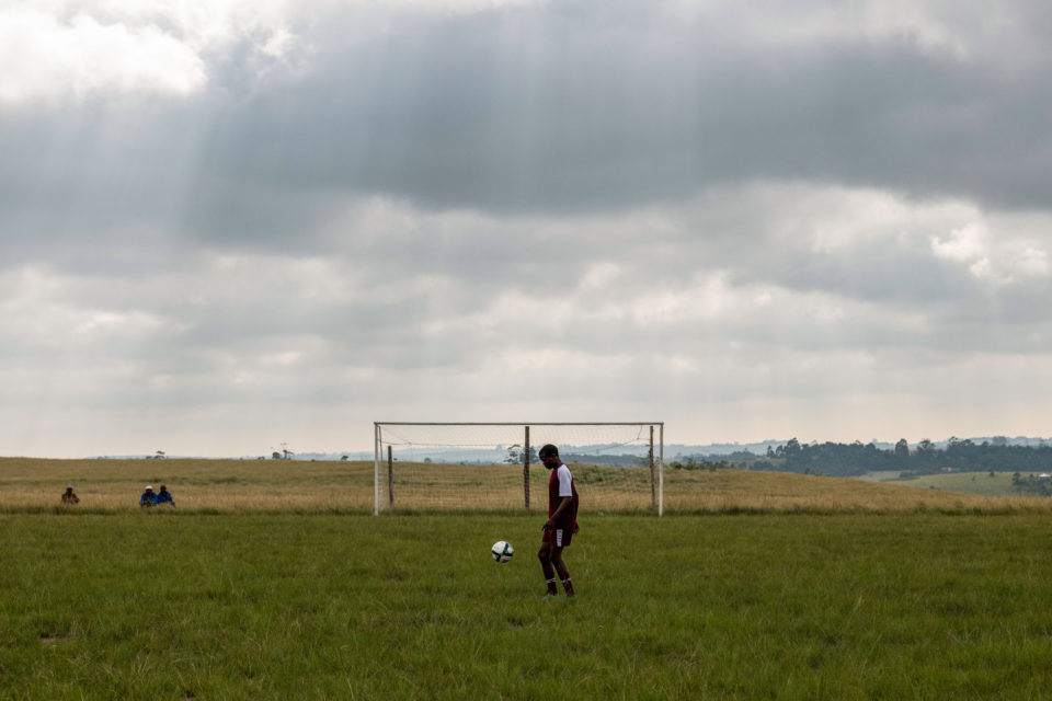 14 April 2019: A player from Cope FC warms up on the thick grass that passes for a football pitch before his team's game in Baleni in the Eastern Cape's Mpondoland.