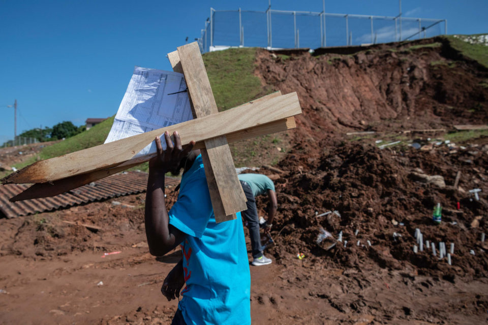 25 April 2019: A family member removes a pair of crosses that were placed at the site where eight bodies were uncovered after a mudslide behind the Westcliff Secondary School in Chatsworth, Durban, caused a house to collapse.