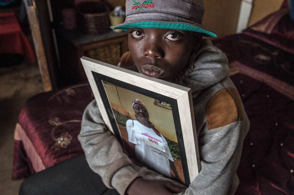 11 April 2019: Sihle Kubayi, 13, holding up a portrait of his grandmother, Patron Kubayi. After witnessing her murder, he and his mother had to find refuge with family members in Vlakfontein, Soweto.
