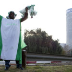 12 June 2010: A Nigerian soccer fan stands with a green painted live chicken in front of the Ponte City building in Hillbrow, Johannesburg during the 2010 World Cup. (Photograph by Per-Anders Pettersson/Getty Images)