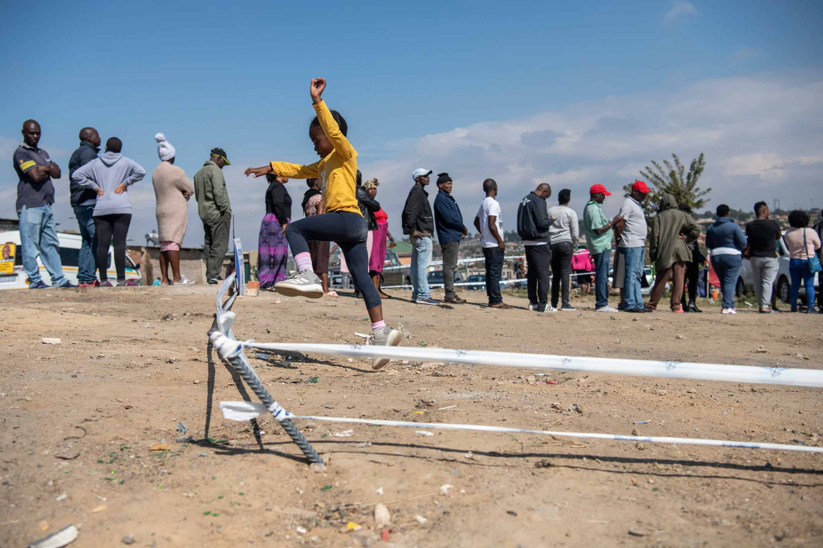 8 May 2019: A young girl plays near a voting station in Alexandra as residents line up to vote in the 8 May elections.