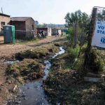 7 May 2019: Rubbish and dirty water stream past a voting station in Kliptown.