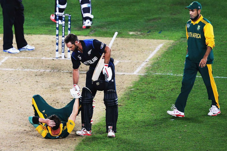 24 March 2015: Grant Elliott of New Zealand helps a gutted Dale Steyn of South Africa up after winning the Cricket World Cup 2015 semifinal against the Proteas at Eden Park in Auckland, New Zealand. (Photograph by Hannah Peters/Getty Images)