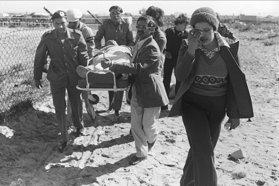 25 August 1976: A seriously injured Christopher Truter, who was shot by the police in Bonteheuwel, Cape Town, is carried to a waiting ambulance. He later died in hospital. (Photograph by Jim McLagan/African News Agency)