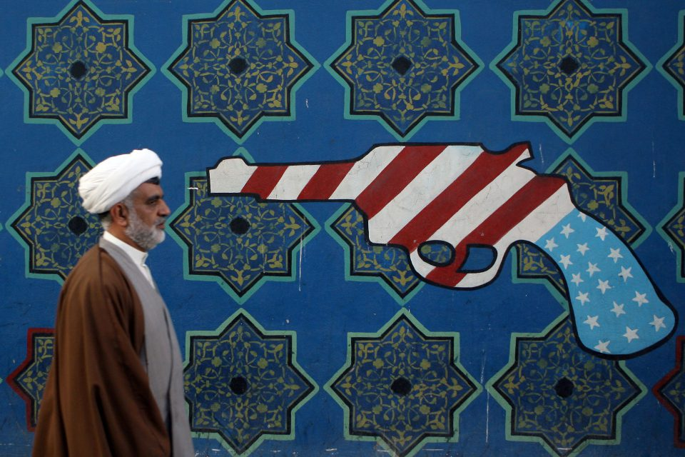 22 February 2007: An Iranian cleric walks past a mural on the wall of the former US Embassy in Tehran. Earlier that week media reports said that the US had plans for bombing Iran, a scenario that is again possible today. (Photograph by Majid Saeedi/Getty Images)