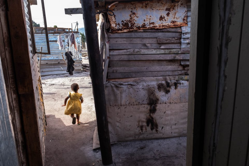 20 June 2019: Caleb Phula's daughter plays outside his home in Siyanyanzela. Residue from a petrol bomb, potentially a politically motivated crime amid growing support for the Socialist Revolutionary Workers' Party, can be seen on the wall in the foreground.