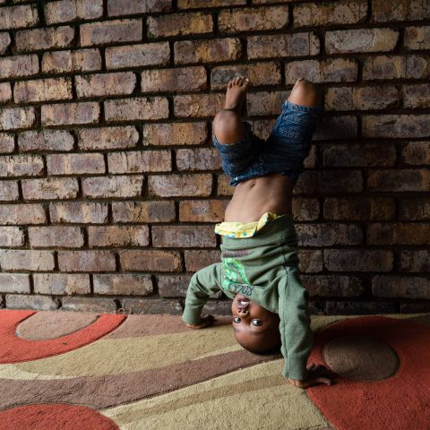 13 March 2019: Four-year-old Zbusiso Ntshangase does a handstand between activities at the early childhood development centre in Germiston run by Noetsie Elizabeth Brink.