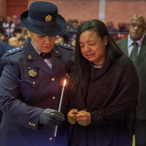 9 July 2019: Shaldene Prins is comforted by a police officer as she prepares to light a candle at the memorial service for her husband, Sergeant Donovan Prins.