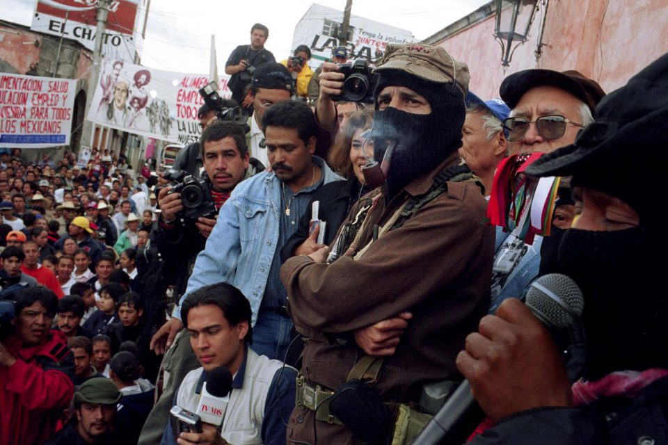 5 March 2001: Subcomandante Marcos, leader of the Zapatista National Liberation Army, smokes a pipe on stage on the way to Mexico City during a Zapatistas tour (Zapatur) in Mexico. (Photograph by Yoray Liberman/Getty Images)