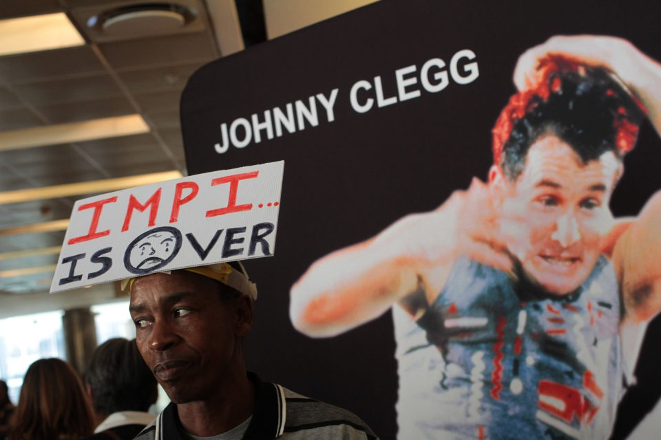 26 July 2019: Banners adorned the outside of the Sandton Convention Centre in Johannesburg for the memorial service of musician and anthropologist Johnny Clegg, who died on 16 July of pancreatic cancer at the age of 66. Clegg fan Ali Gule wore his sentiments on his cap, citing Clegg's 1981 hit, Impi.