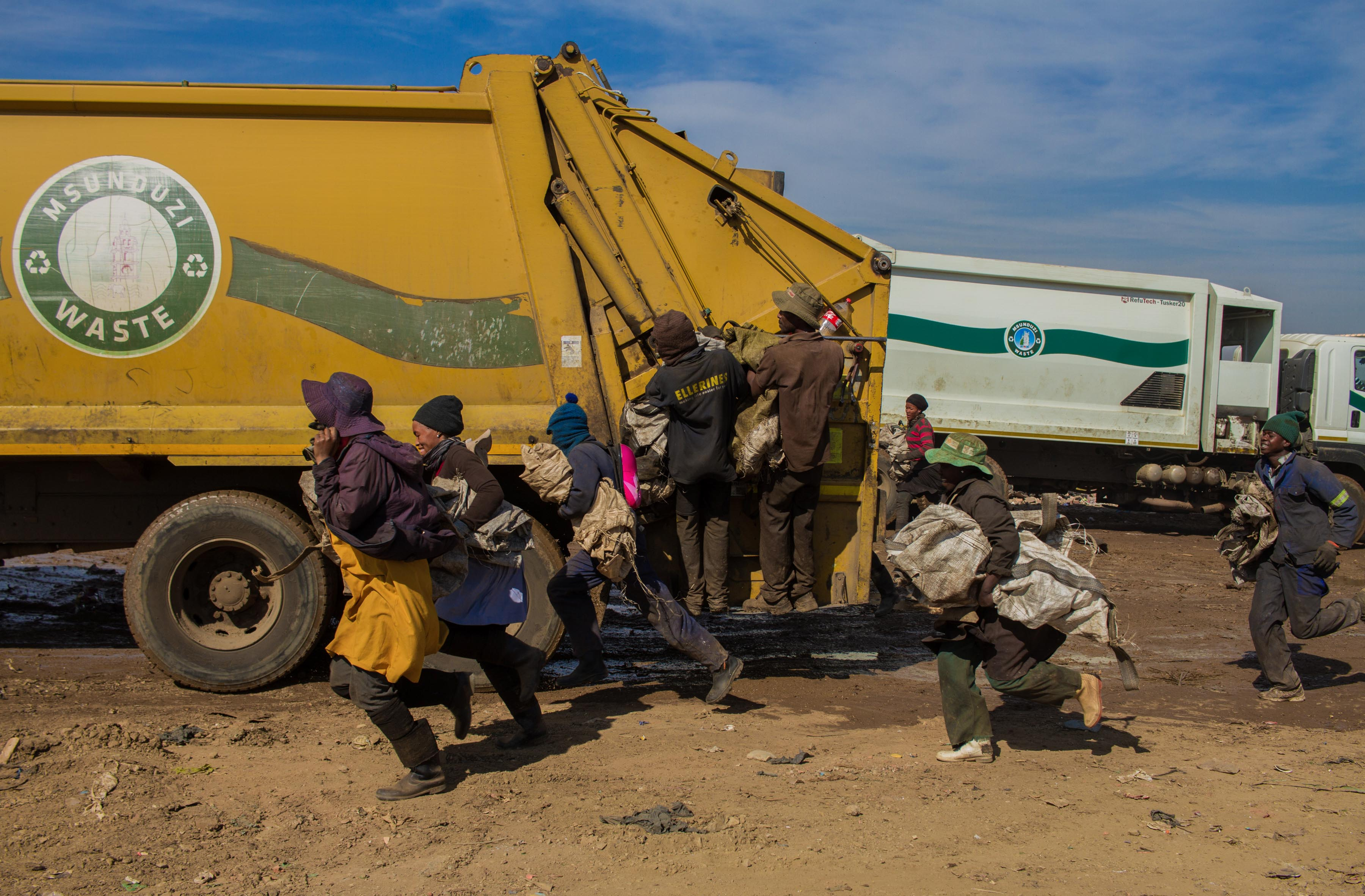 18 July 2019: Some waste pickers jump on to arriving compactor trucks while they are still moving in an attempt to get to the refuse first. It's dangerous work and several pickers have died on site.