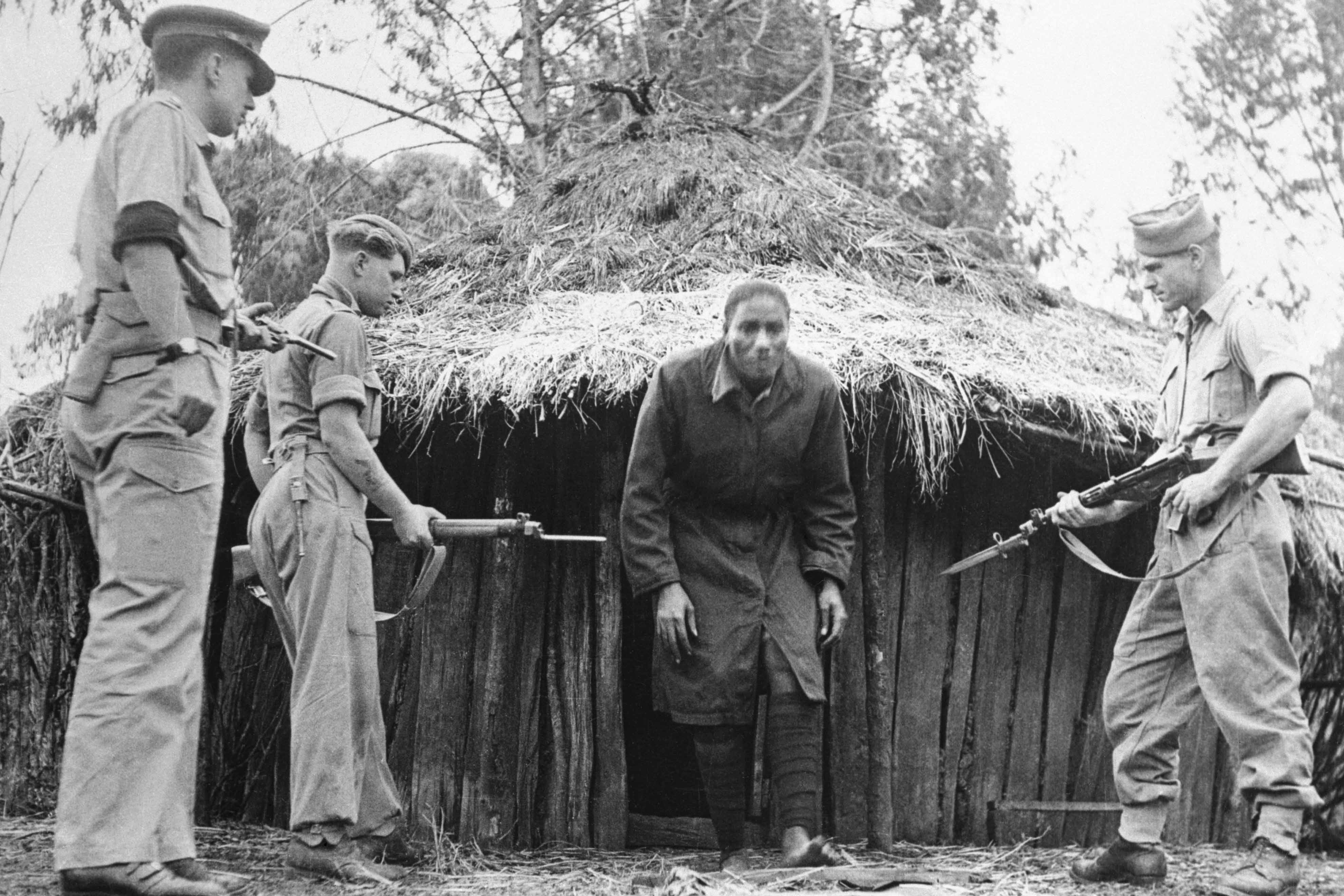 Undated: Members of the Lancashire Fusiliers apprehending a man suspected of being a 'Mau Mau' freedom fighter in Kenya during colonial times.
