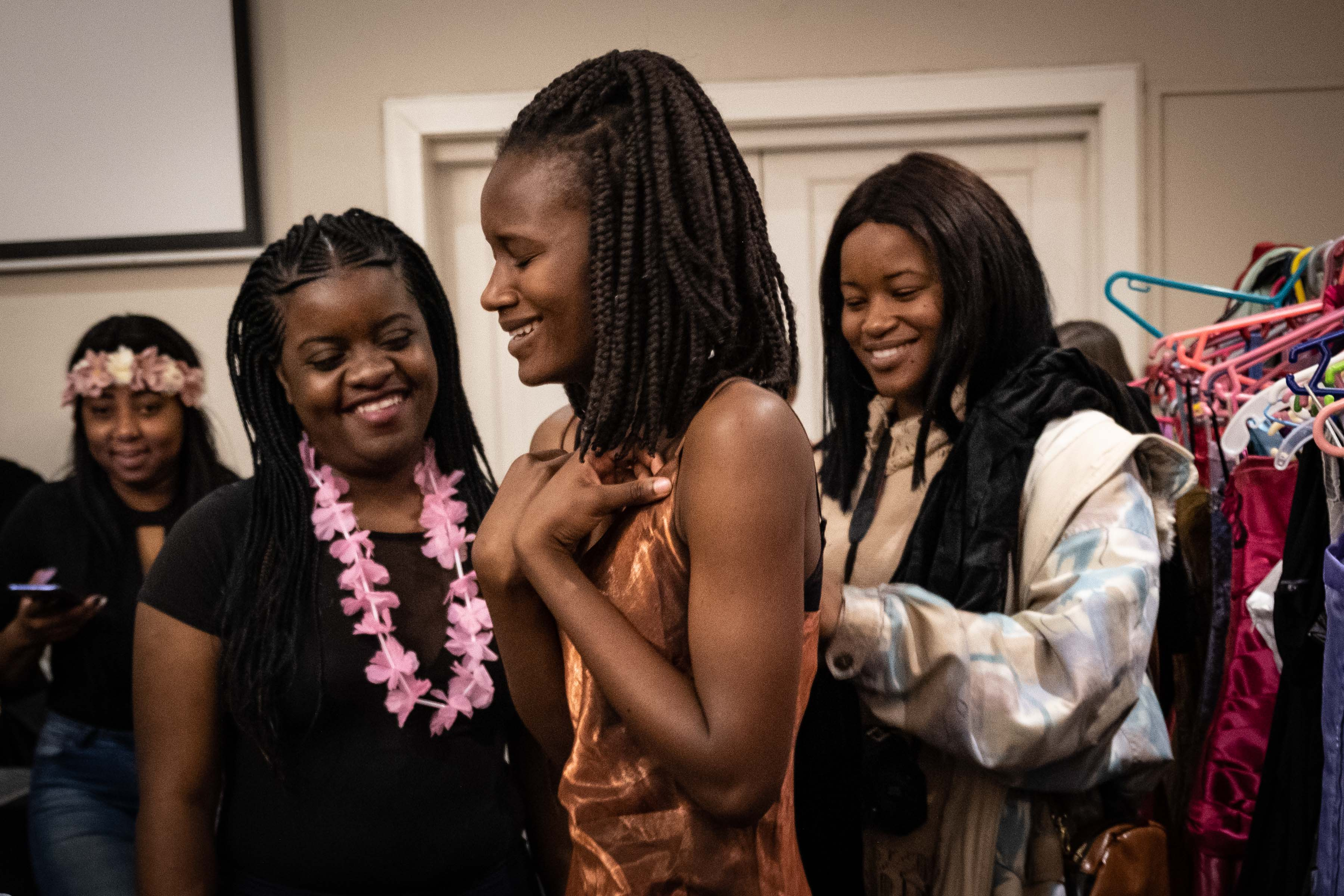 9 August 2019: Goodness Muntswu smiles as she tries on one of the many options. A volunteer from The Cherry Blossom Project and Goodness's sister, Dembe (right), enjoy the moment with her.