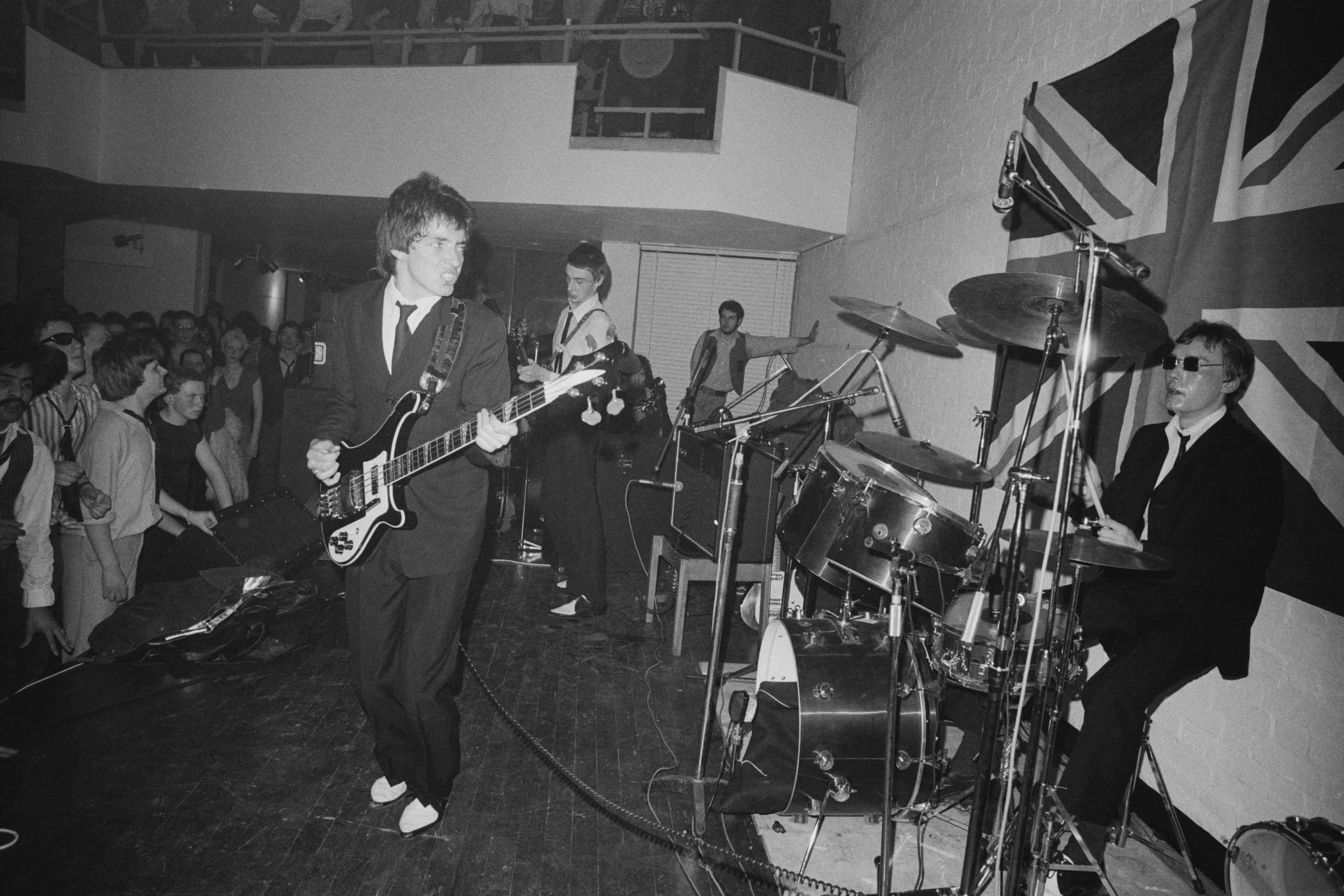 29 April 1977: The Jam on stage at the Royal College of Art in London, England, in front of a large Union Jack flag. (Photograph by Erica Echenberg/Redferns)