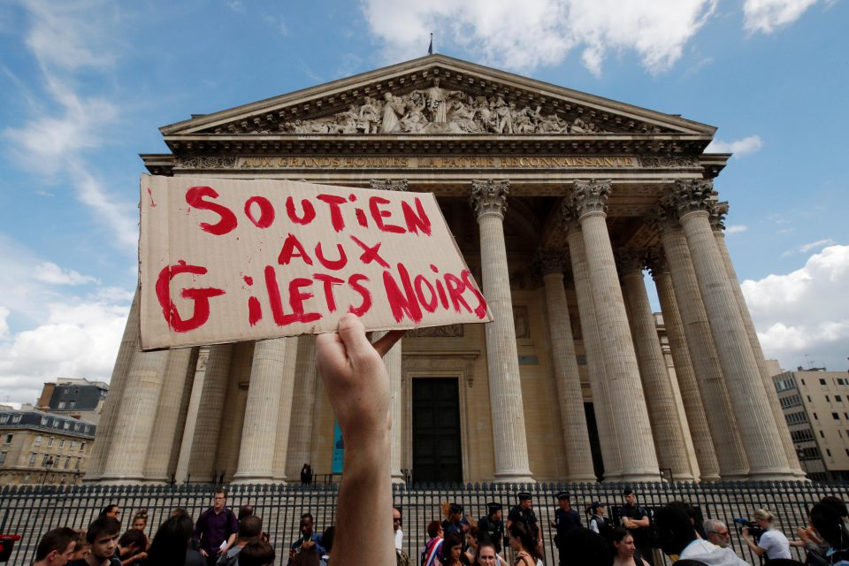 12 July 2019: A man holds a placard saying 'Support to the gilets noirs' in front of the Panthéon in Paris, which undocumented migrants occupied to highlight their standing in France and the harm French forces have done in their homelands. (Photograph by Reuters/Philippe Wojazer)
