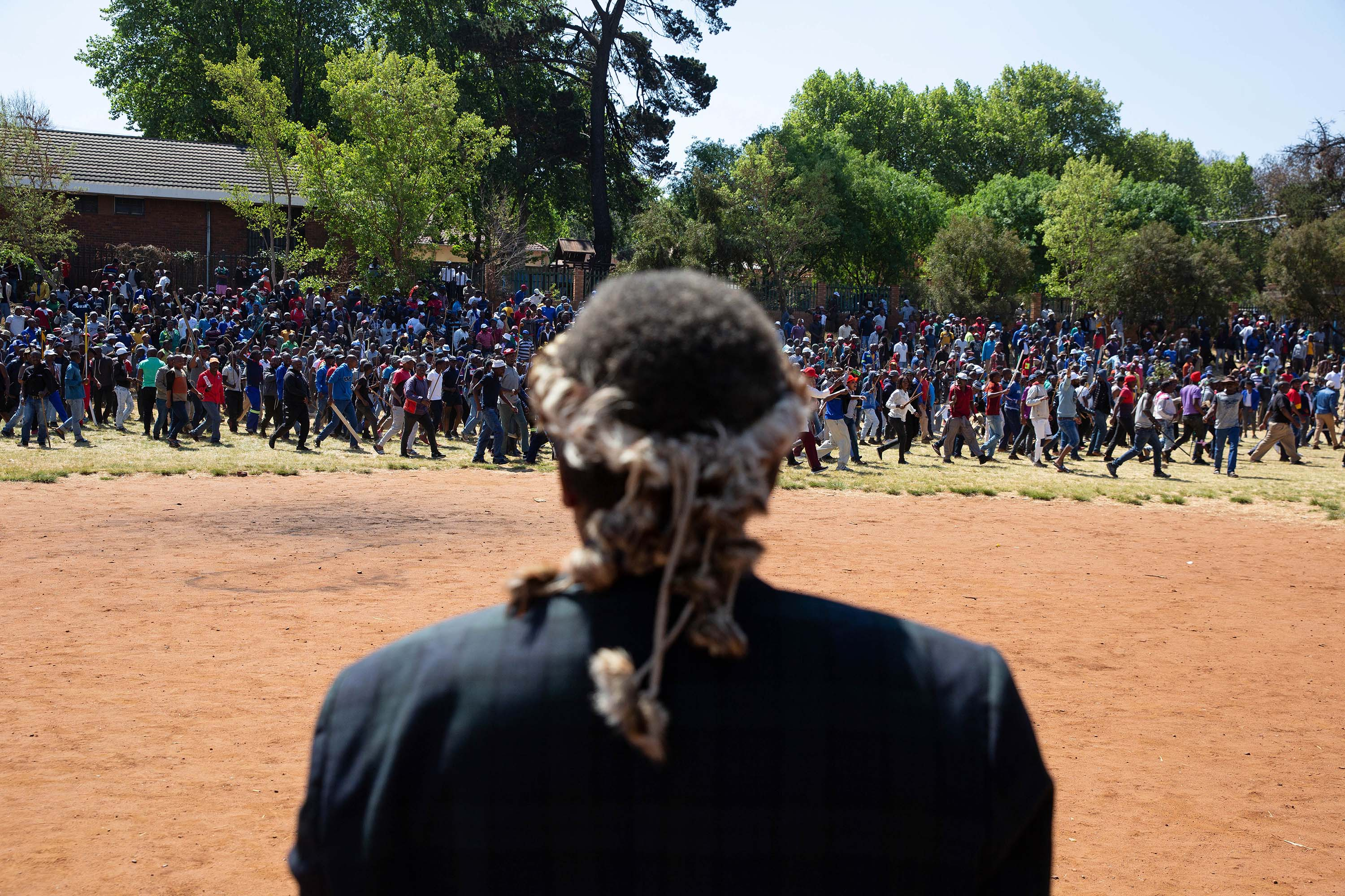 8 September 2019: An induna watches as a dissatisfied crowd of men leaves Murray Park during Mangosuthu Buthelezi's speech. (Photograph by James Oatway)