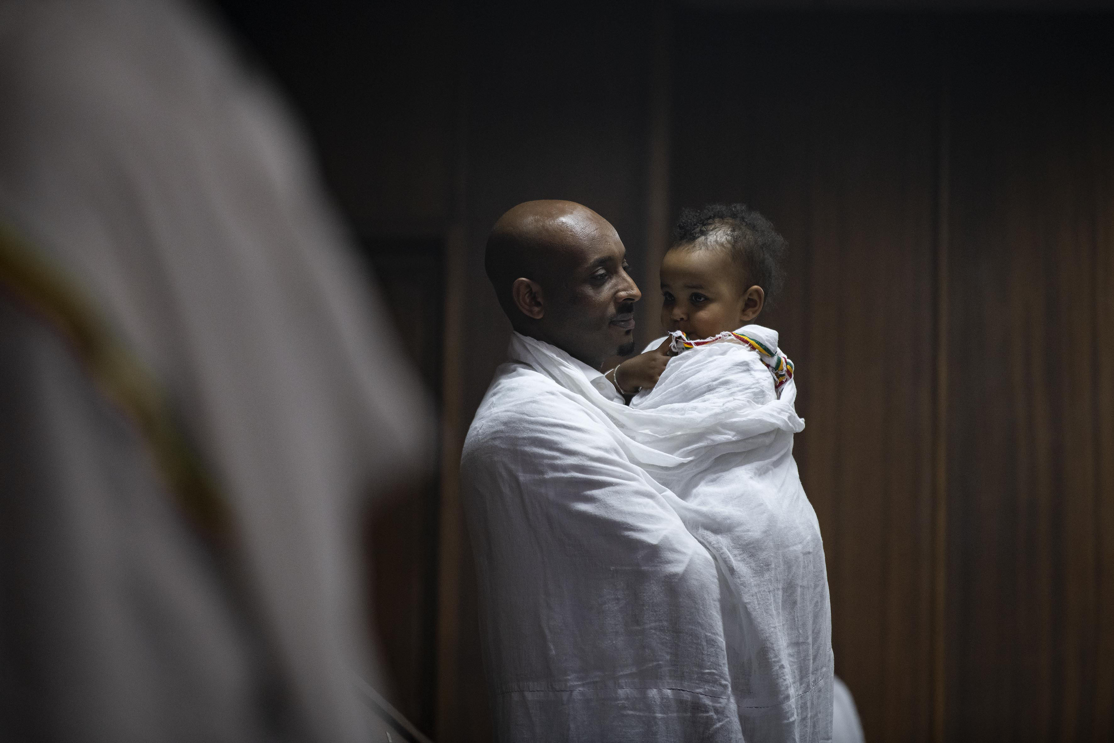 12 September 2019: An Ethiopian man dressed in traditional clothing cradles his baby during a prayer during the New Year service at the Ethiopian Orthodox Tewahedo Church in Berea, Johannesburg.