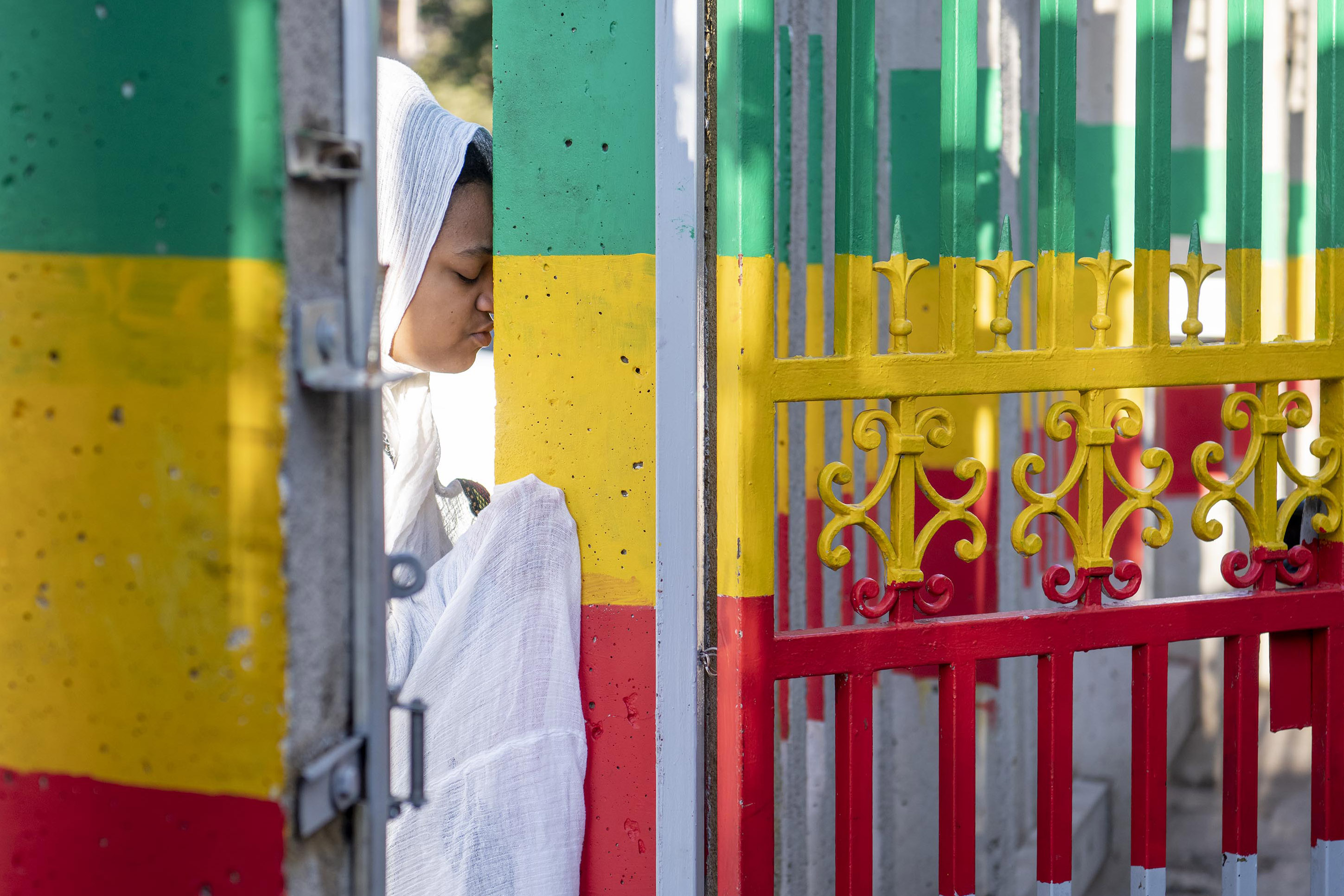 12 September 2019: An Ethiopian woman saying a prayer at the gate of the Ethiopian Orthodox Tewahedo Church.
