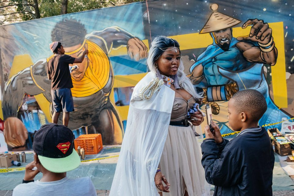 24 September 2019: Boitumelo Rametsi dressed as Storm from X-Men in front of graffiti art of South African superhero Kwezi created by Breeze Yoko at Comic Con Africa in Midrand, Johannesburg. (Photograph by James Puttick)
